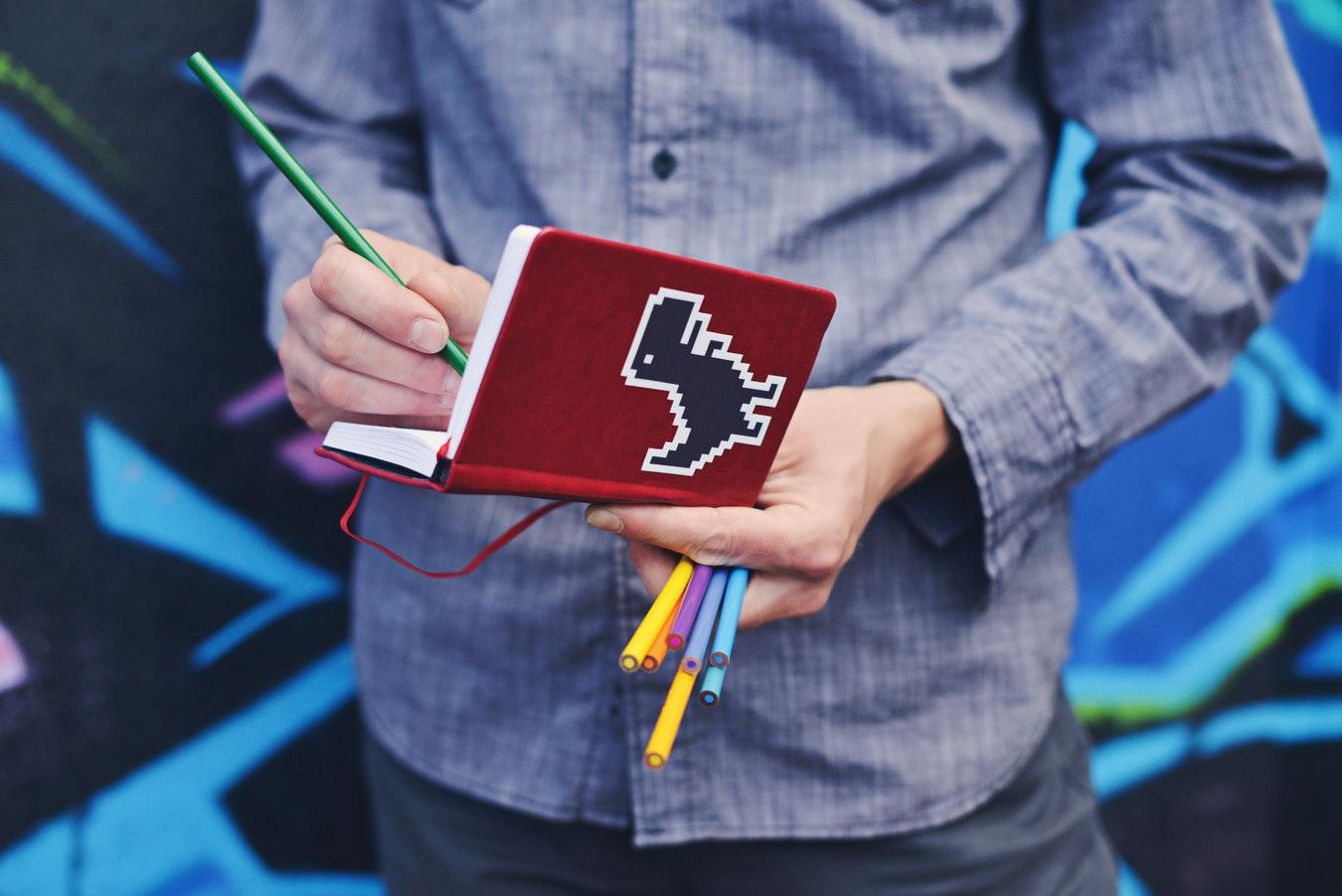 homem-escrevendo-caderno-com-desenho-dinossauro-dicas-redação-enem