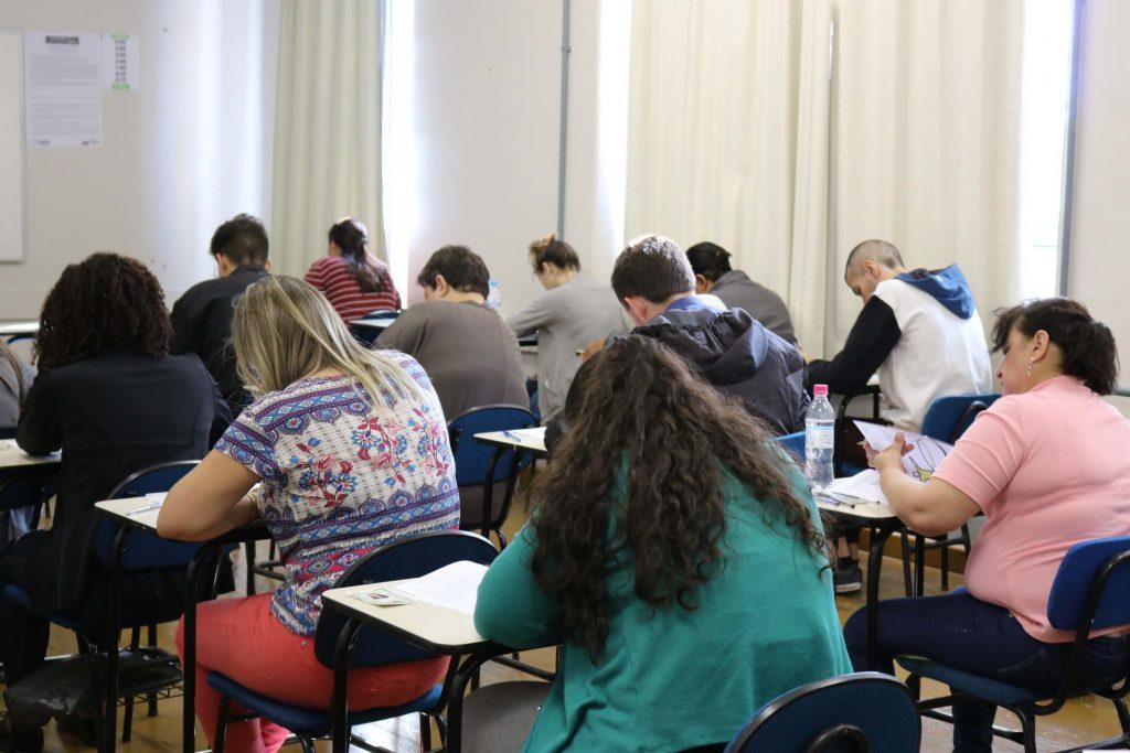 alunos, de costas, realizando prova em uma sala de aula