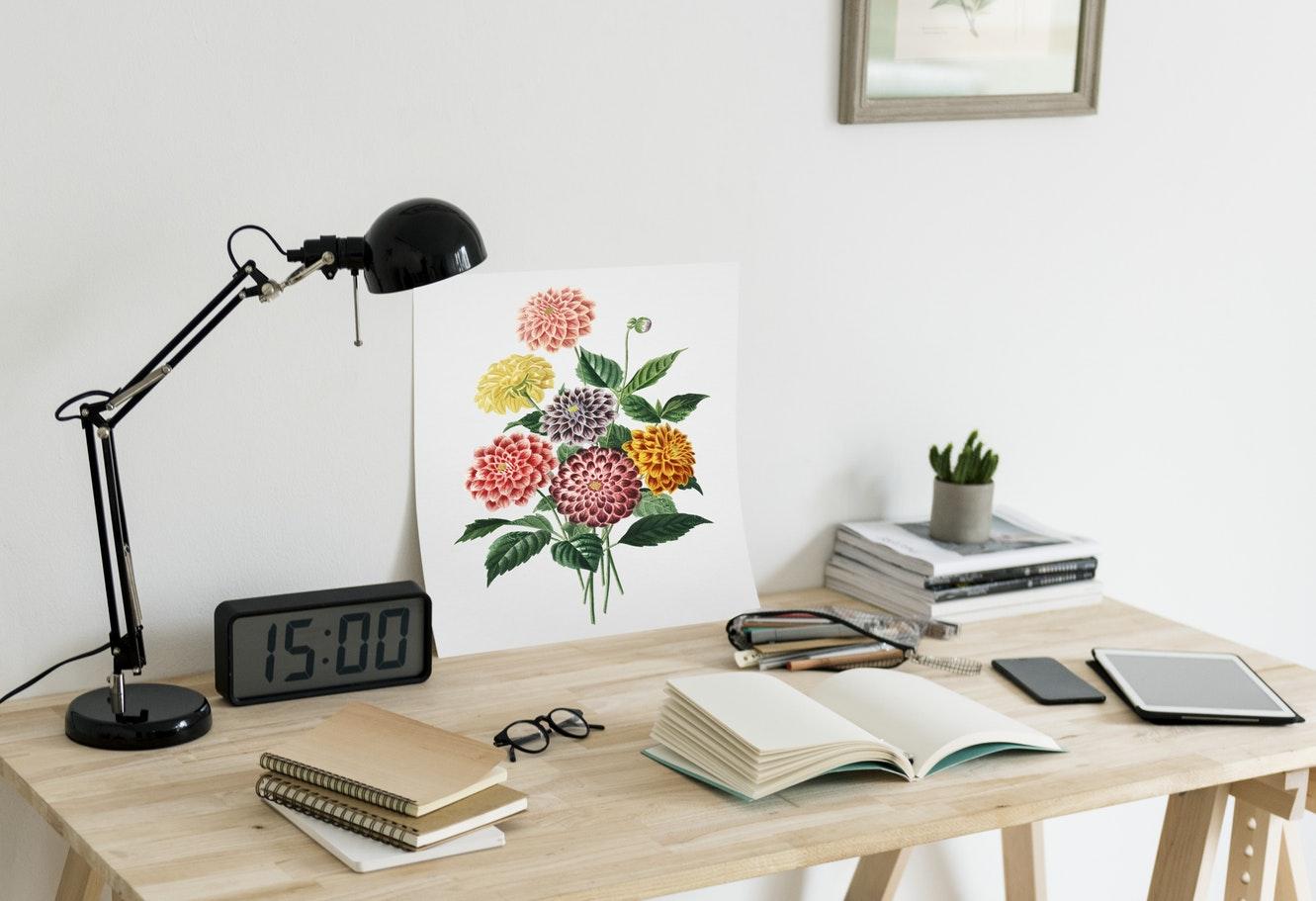 rotina de estudos: mesa organizada, com relógio, luminária, canetas e livros.
