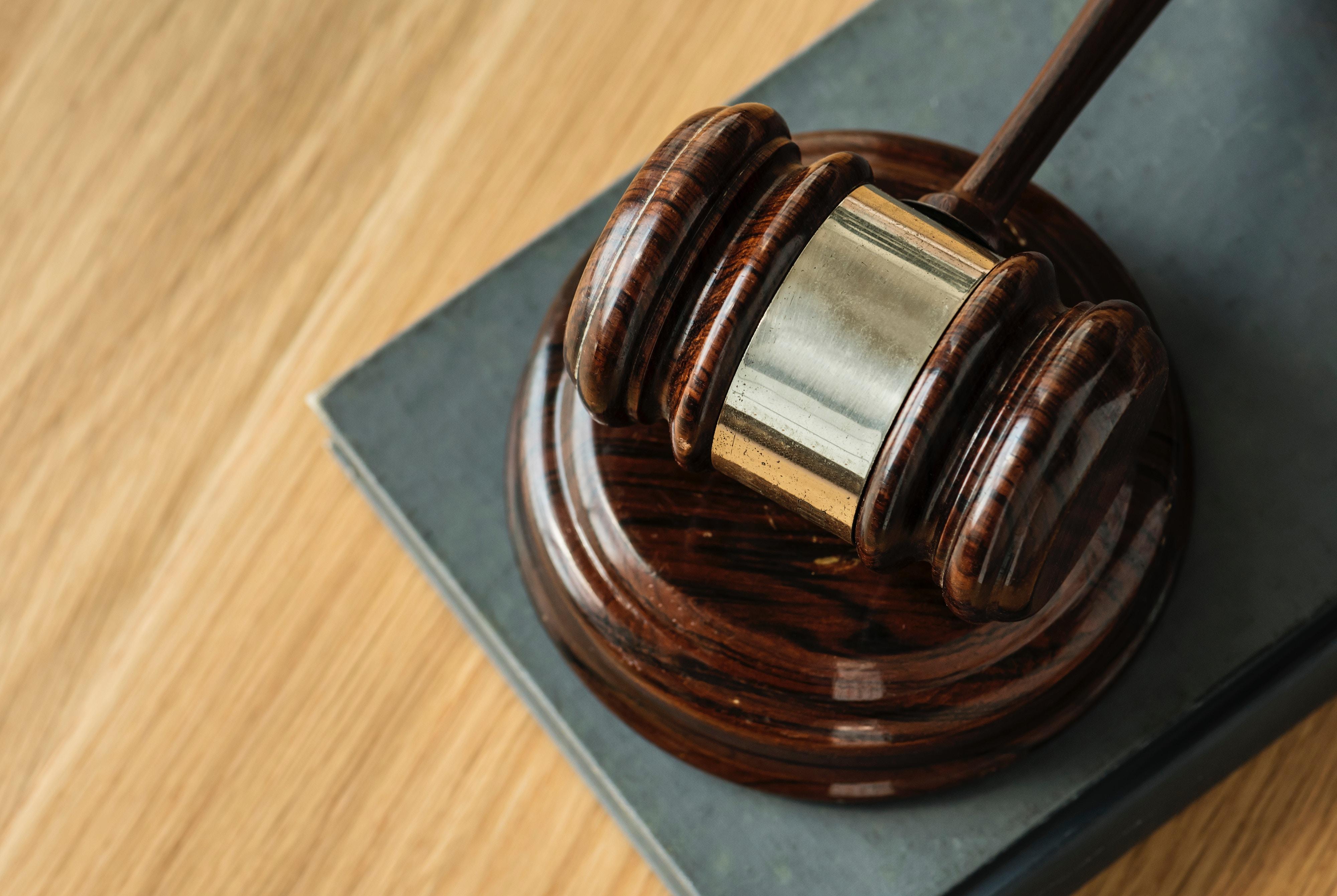 martelo utilizado em audiências judiciais em cima de uma mesa