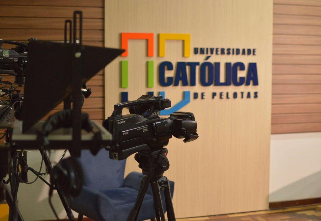 UCPel e as novas gerações: câmeras da TV UCPel em frente ao logo da Universidade