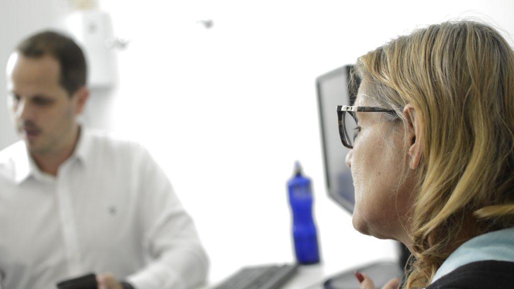 Pacientes Jurídicos UCPel: em primeiro plano, paciente jurídica. Ao fundo e desfocado, aluno da UCPel presta atendimento
