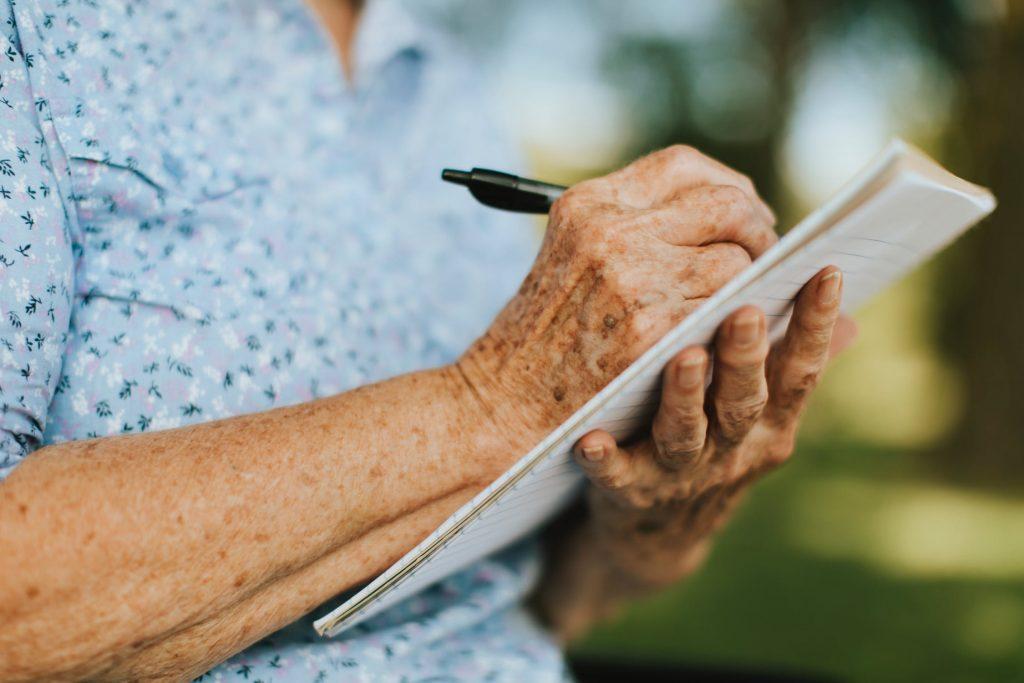Benefícios estudar terceira idade: idosa escrevendo em caderno
