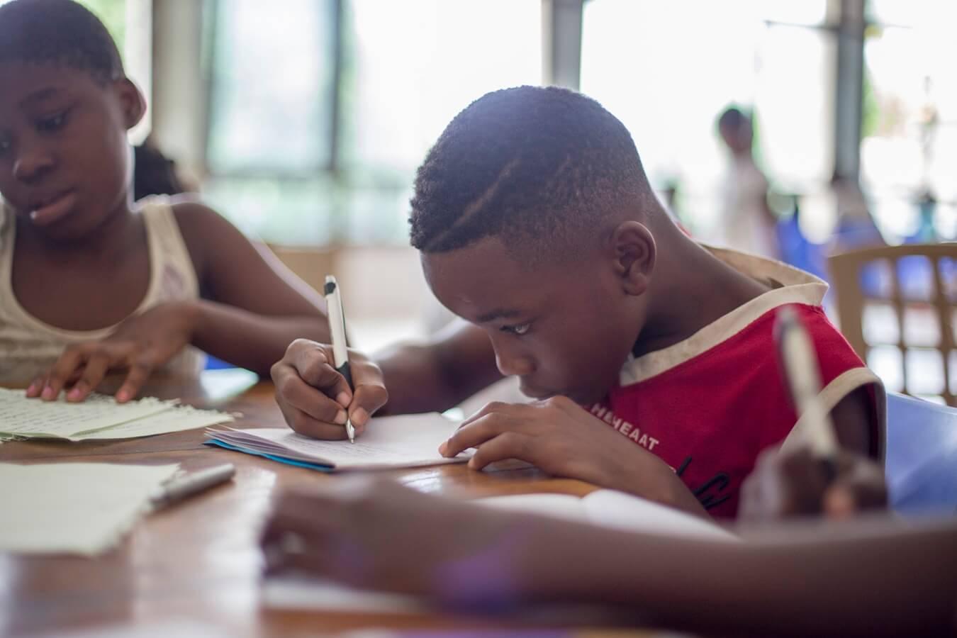 estágio em psicologia: menino escrevendo em caderno