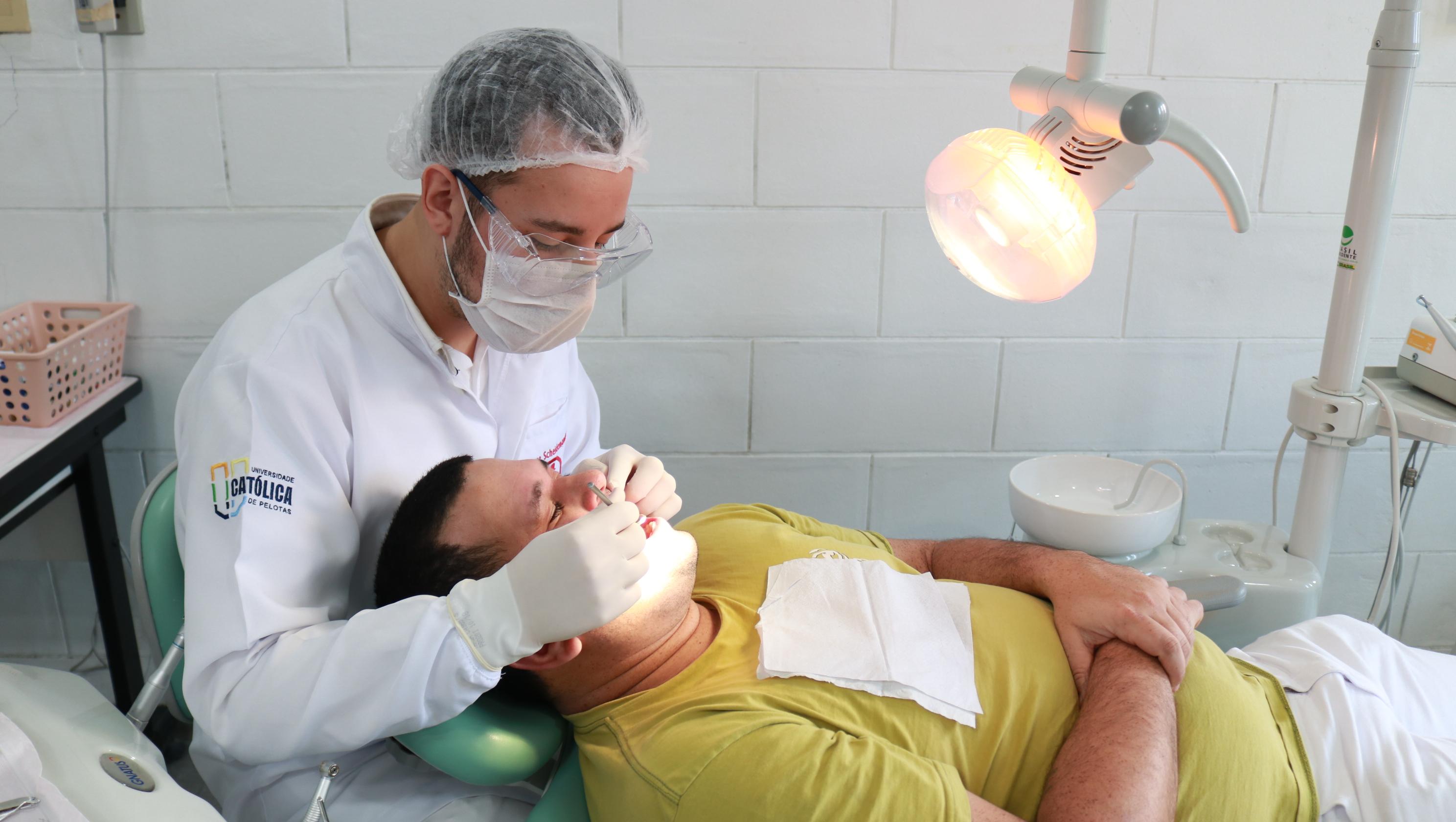 acadêmico da odontologia UCPel realizando atendimento a paciente