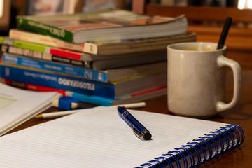 caderno aberto em cima de uma mesa com uma caneta em cima, uma xícara com colher ao lado e outros livros à frente