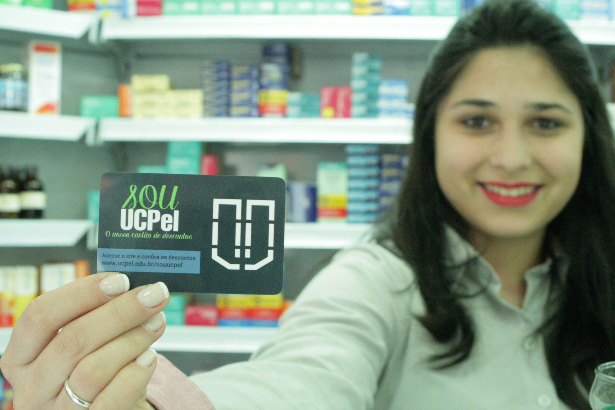funcionária-segurando-cartão-souucpel-remédios-ao-fundo