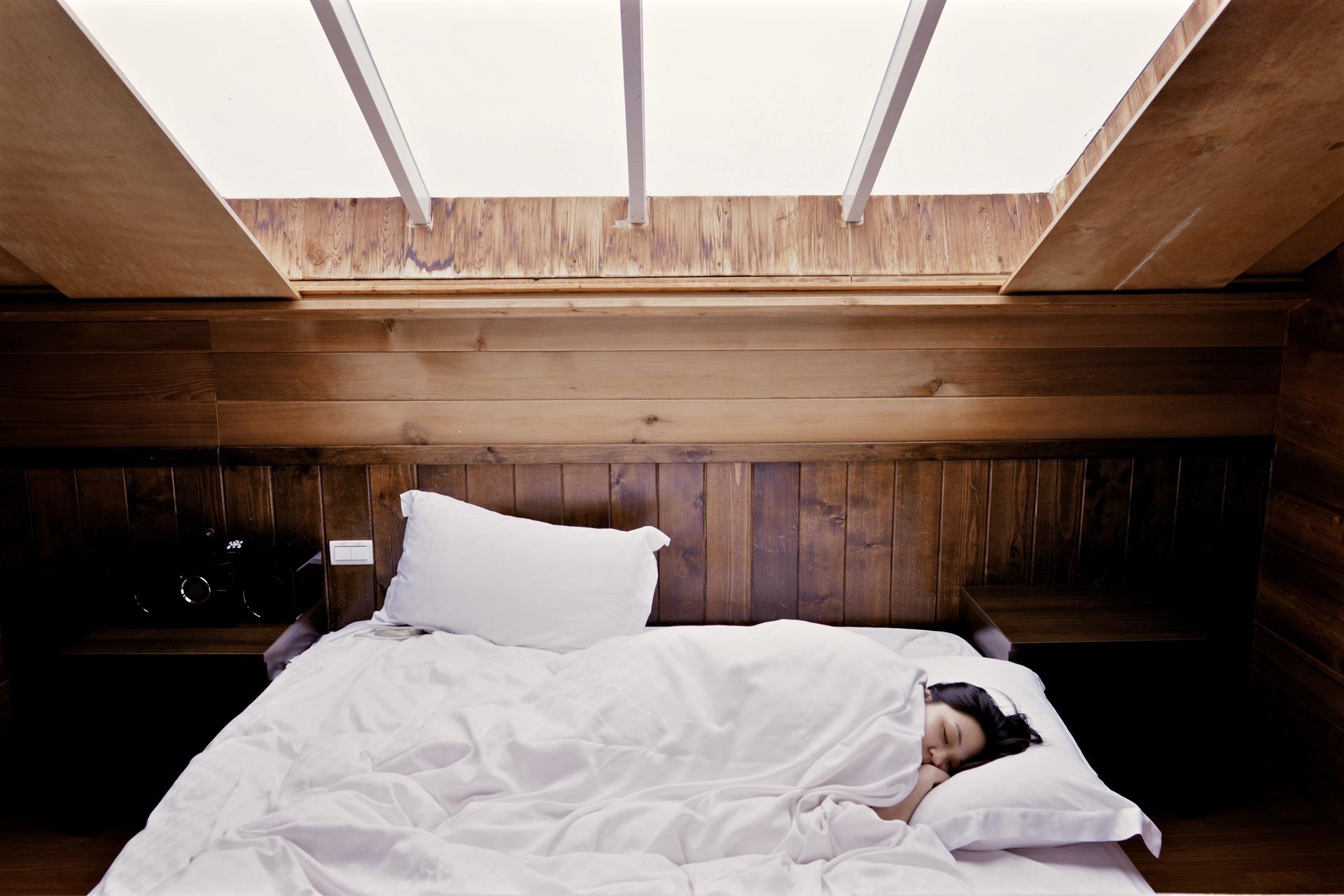 pessoa dormindo em uma cama com lençóis brancos