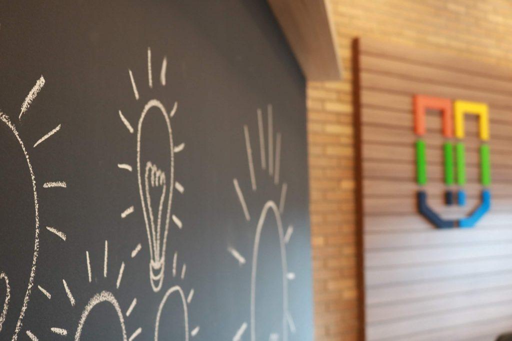 parede com lâmpadas desenhadas, ao fundo, logo da UCPel