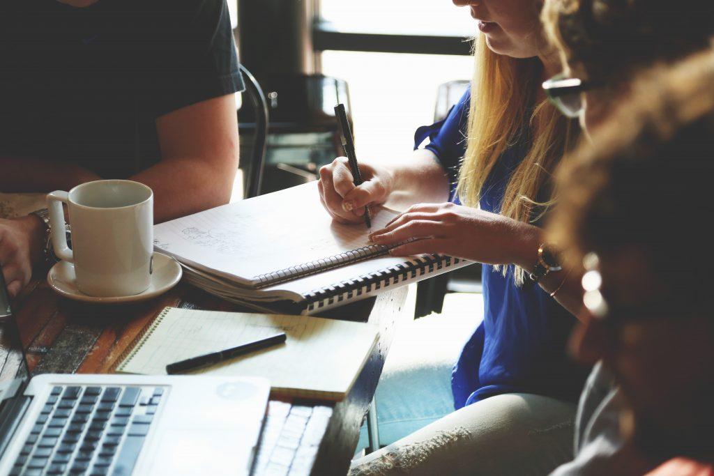 mulher-escrevendo-em-grupo-de-estudos