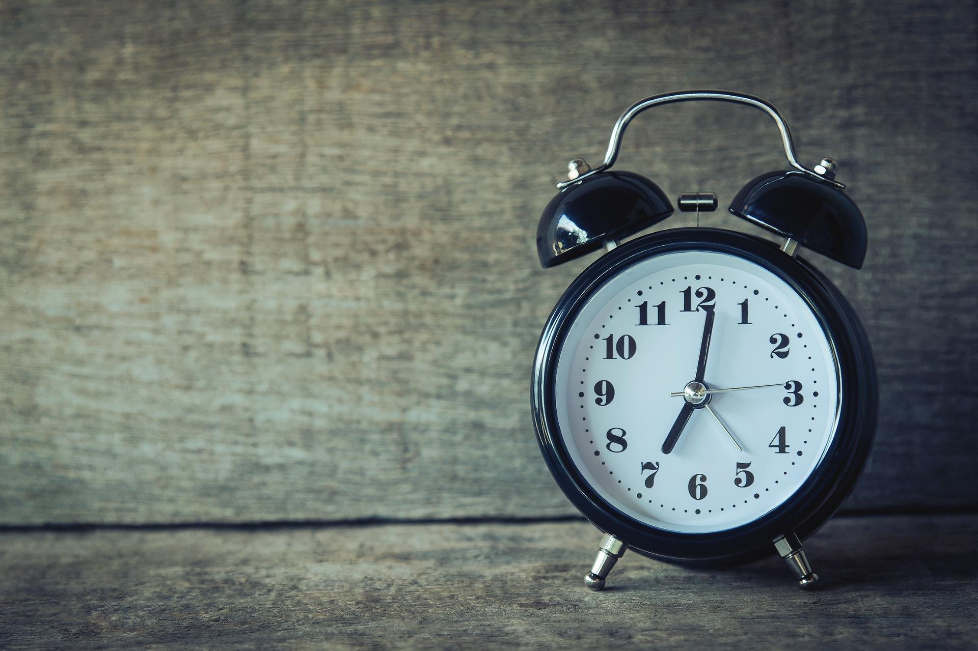 relógio preto localizado à direita da imagem, em um fundo de madeira