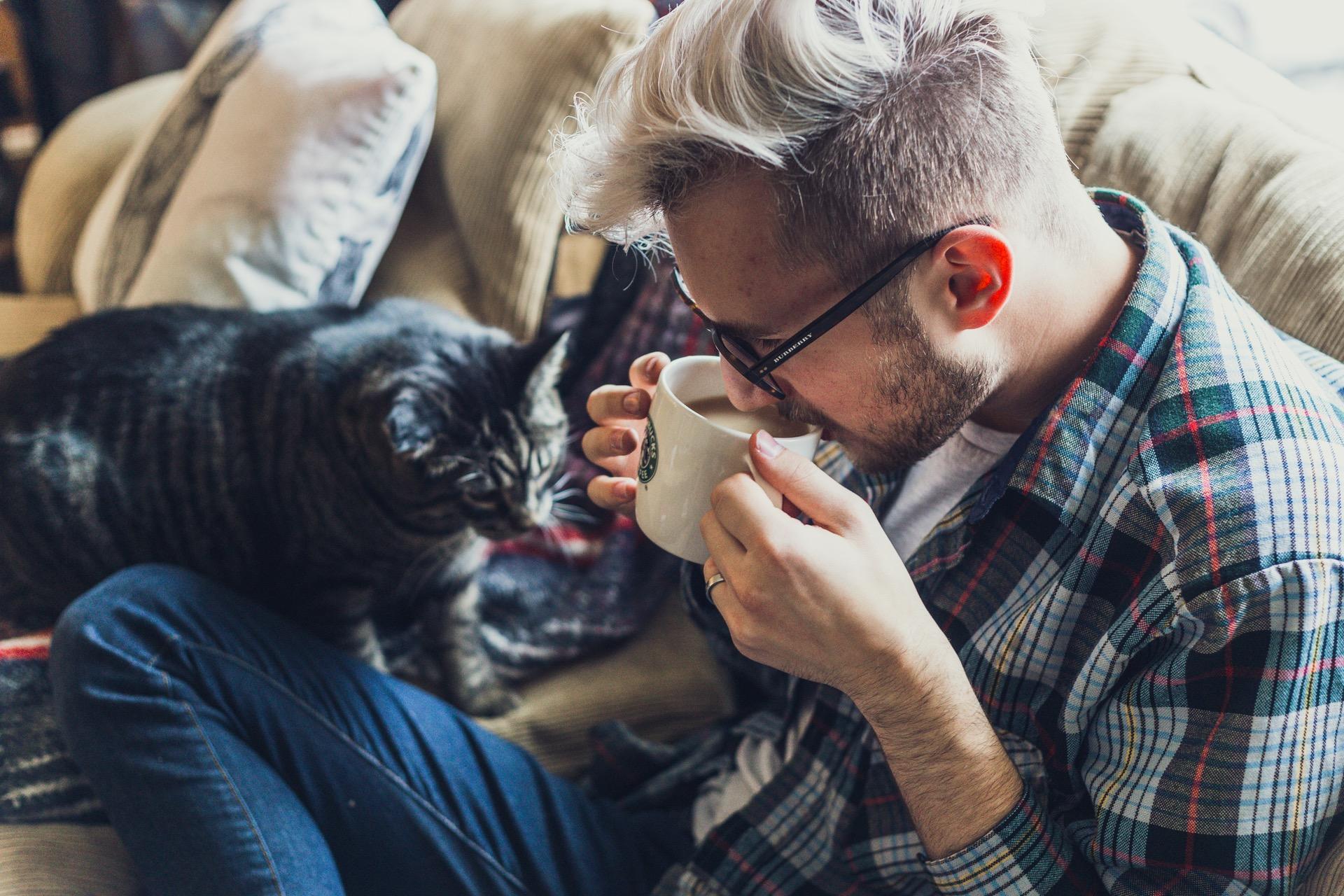homem loiro e com óculos tomando café, sentado em um sofá com seu gato ao lado