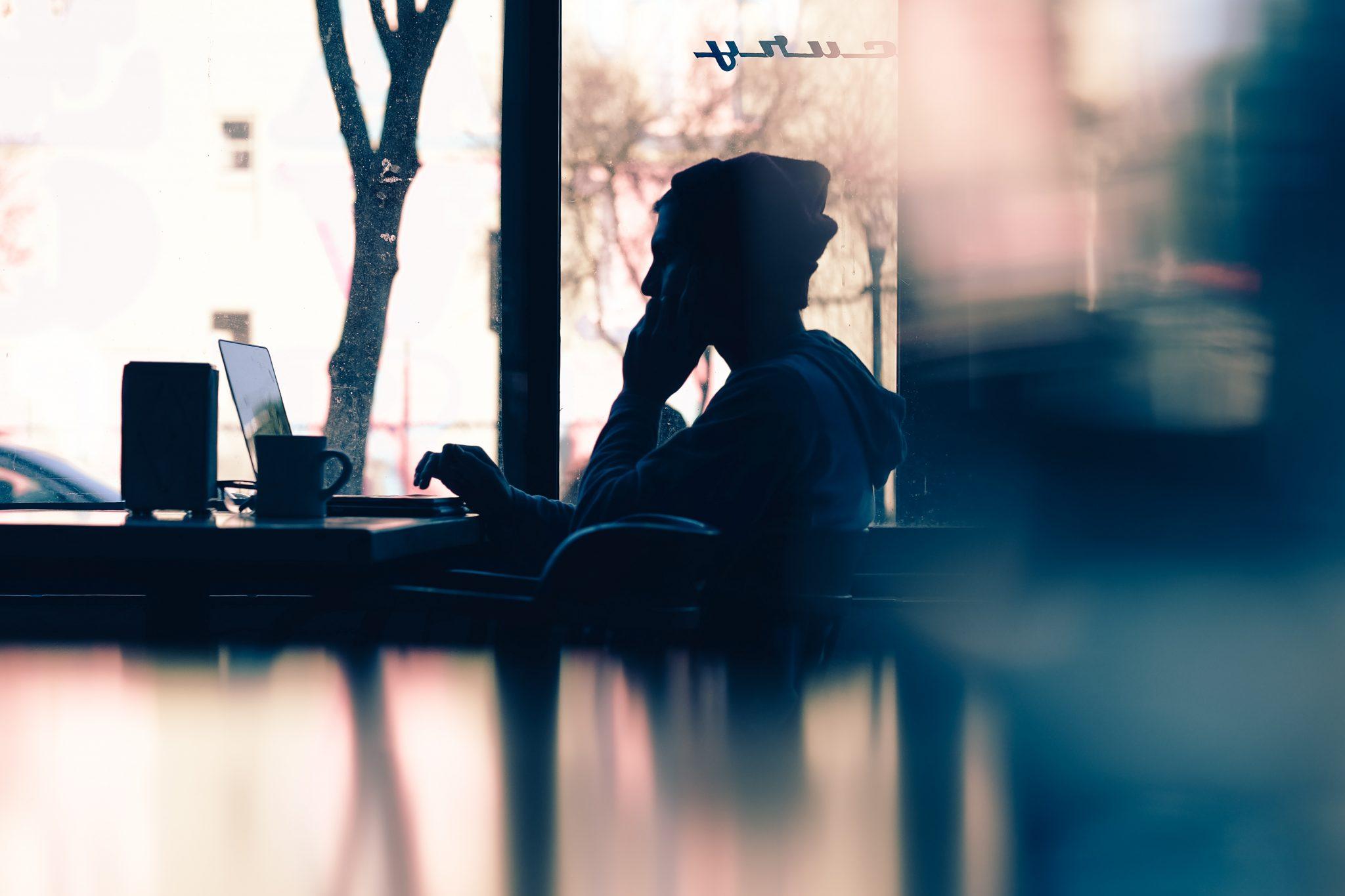 menino sentado em uma mesa, ao lado da janela, utilizando o computador e falando ao telefone