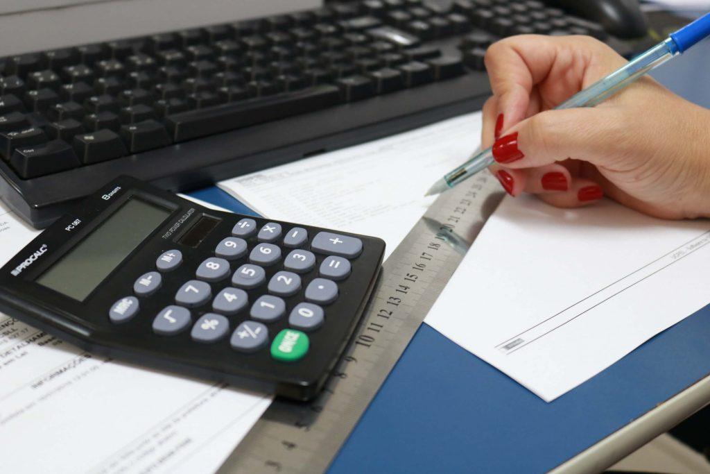 Ciências Contábeis UCPel: calculadora em primeiro plano e mão escrevendo com caneta