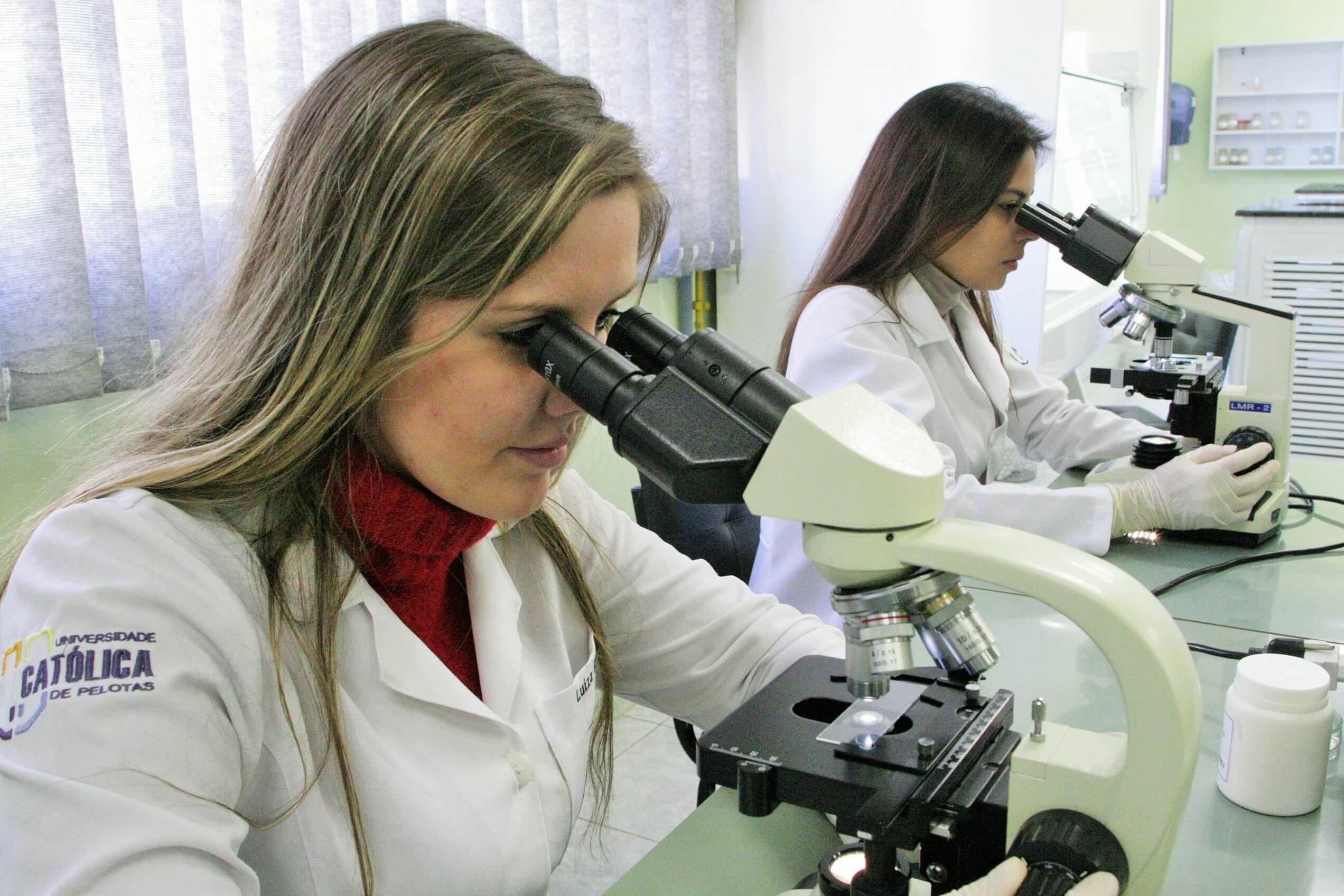 Guia do Estudante: estudantes de farmácia olham através de microscópio
