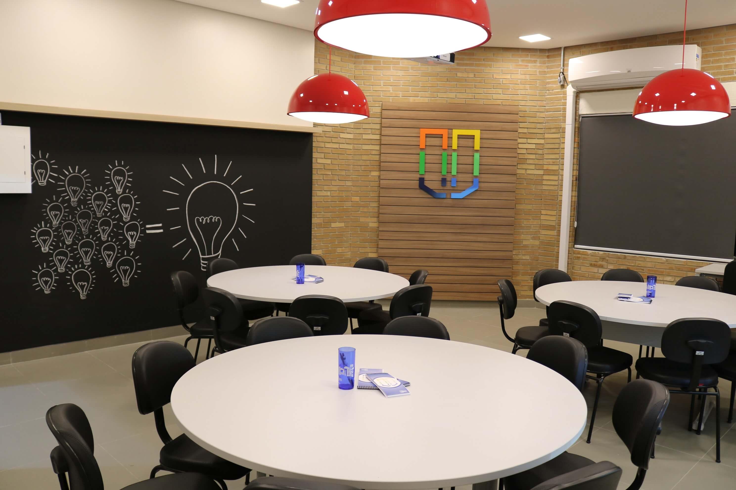 Nova sede do Ciemsul no Parque Tecnológico, mesas para grupos e ao fundo parede com o logo da Universidade.