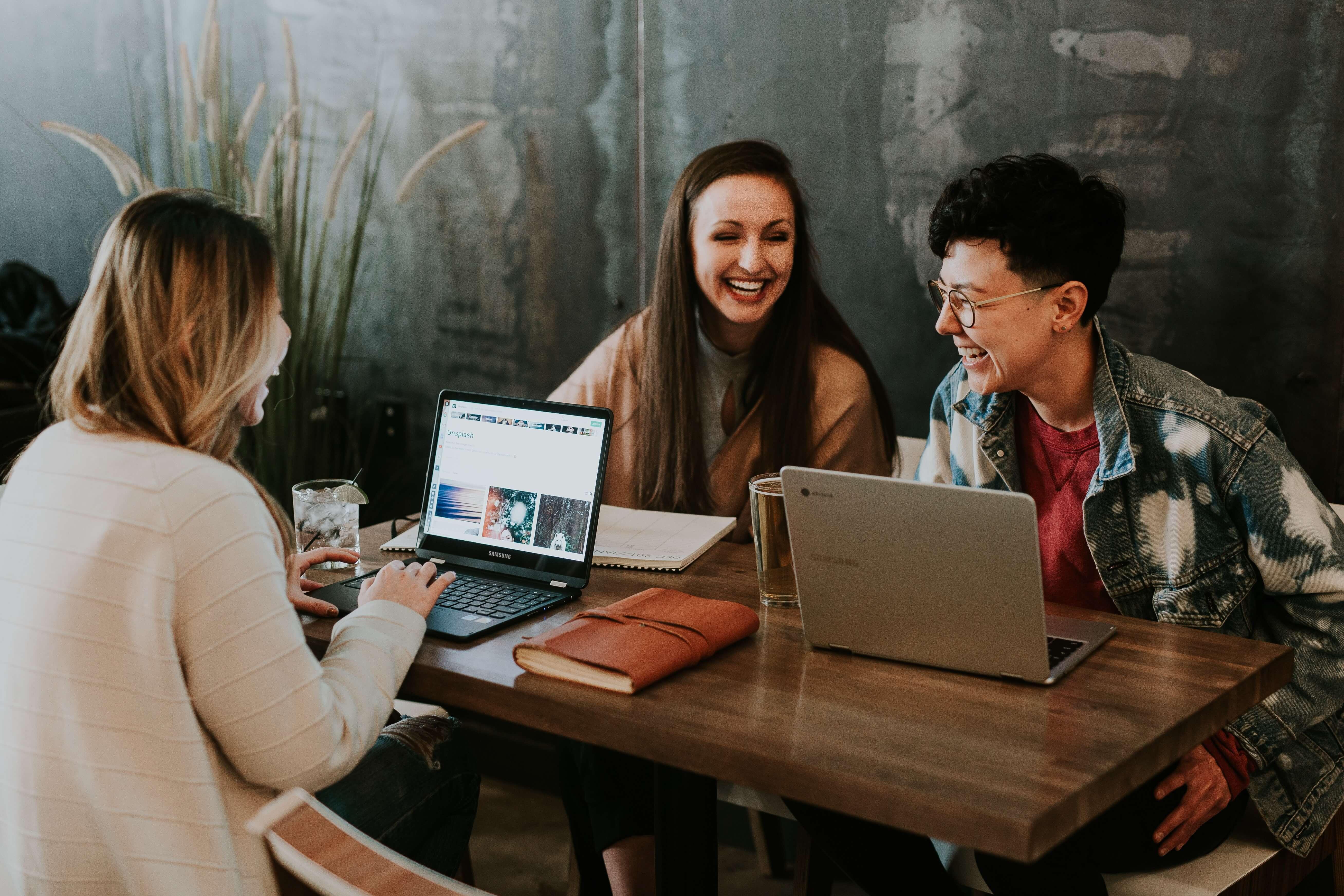 entrar na faculdade: três jovens rindo e utilizando o computador.
