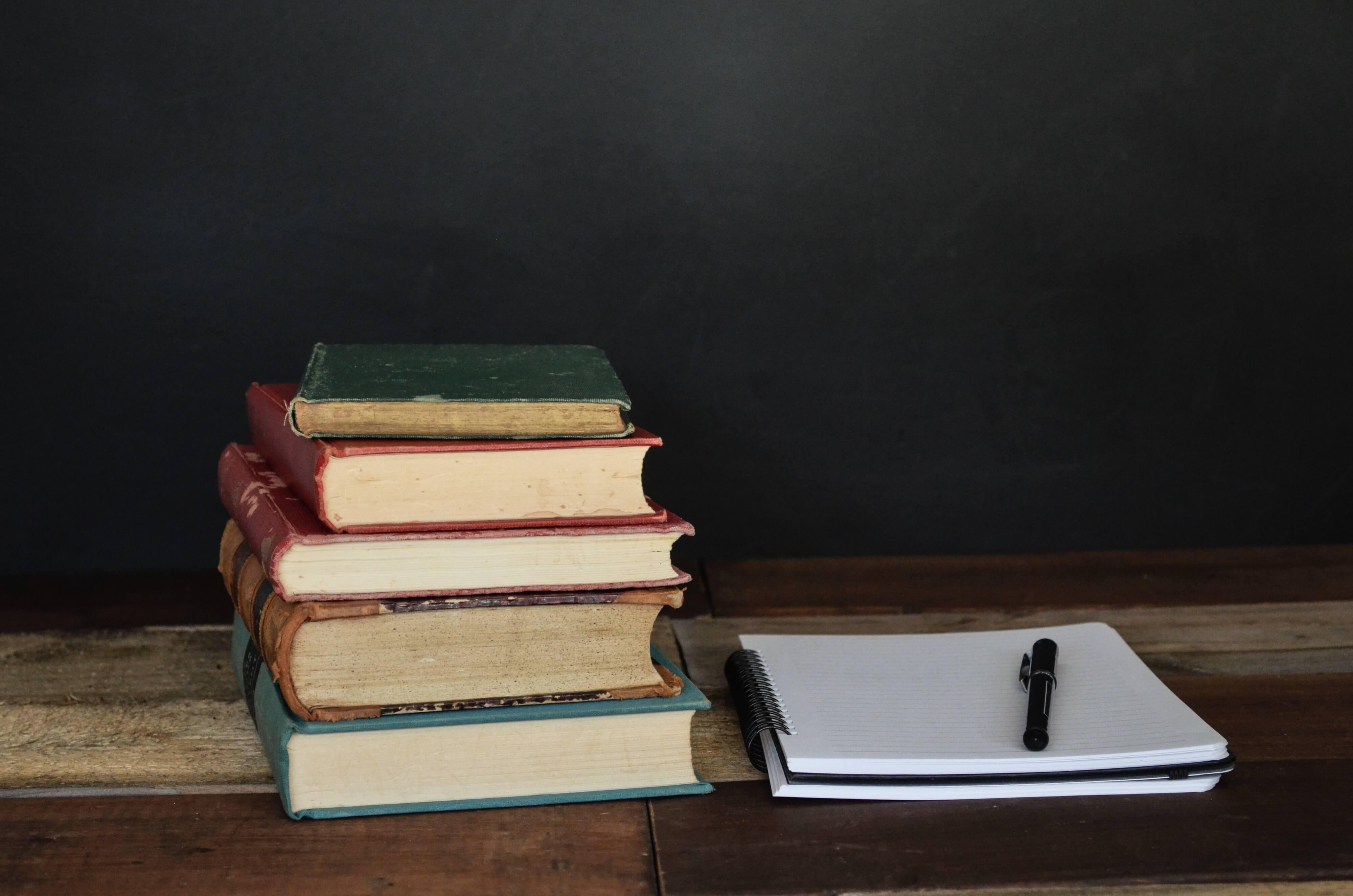 pilha de livros à esquerda e, à direita, caderno com caneta em cima