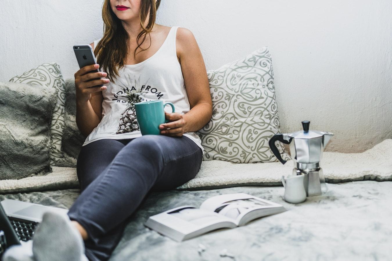 pessoa romando café com livro sobre acama - rotina de estudos