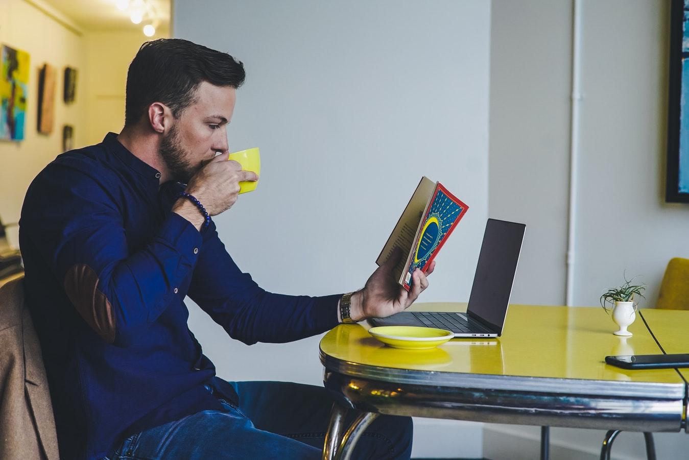 rotina de estudos: homem sentado à mesa, tomando café e lendo um livro.
