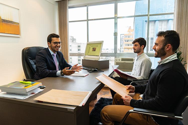 advogado homem atendendo dois clientes em uma sala