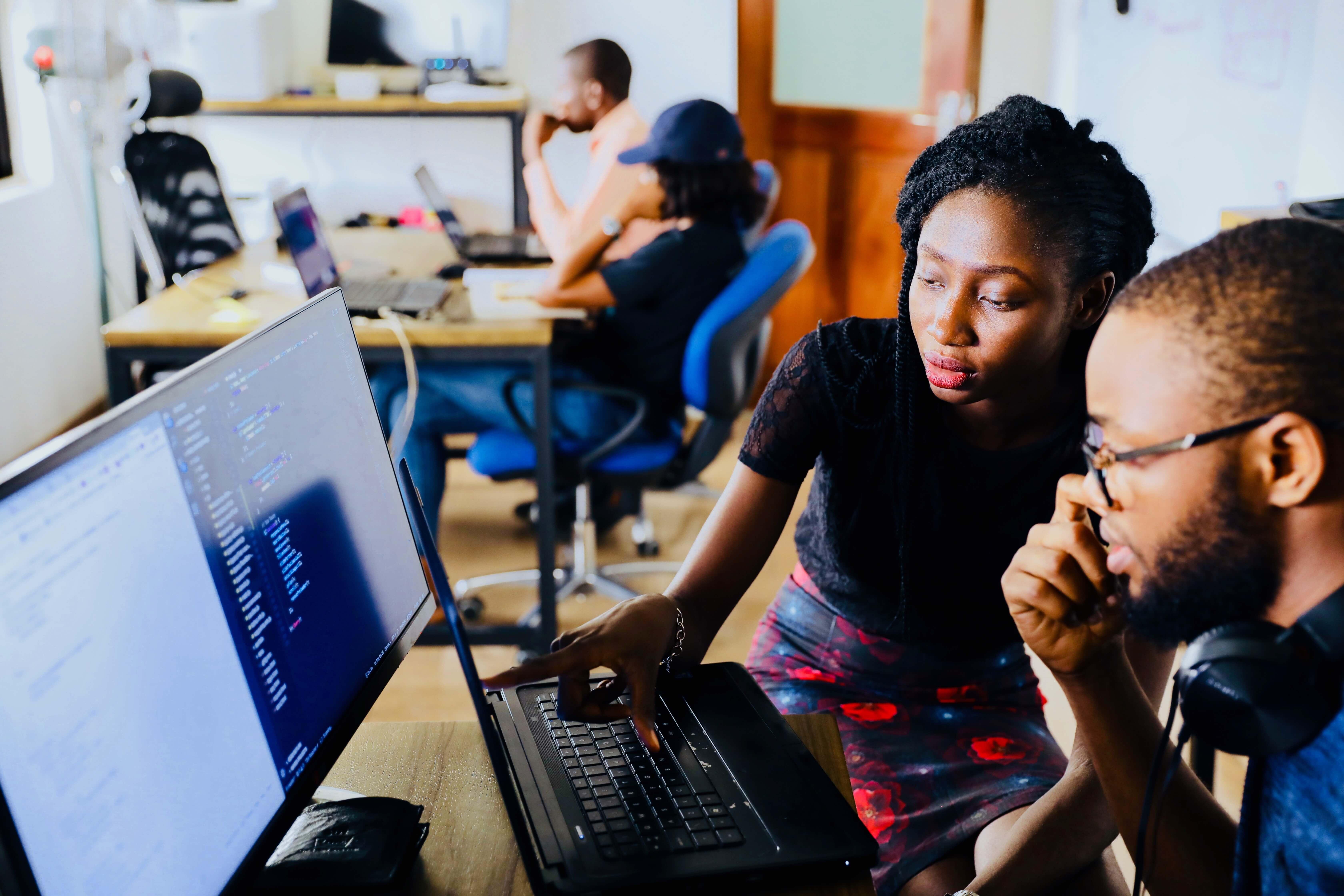 um homem e uma mulher sentados à frente de um computador, conversando e apontando