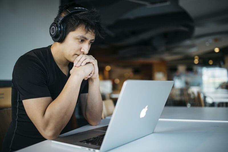 Menino com fones de ouvido lendo em frente ao computador