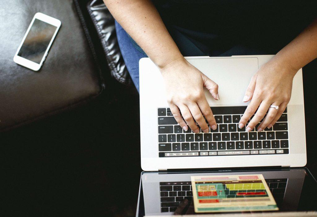 Currículo Lattes: mãos digitando em computador, vistas de cima.