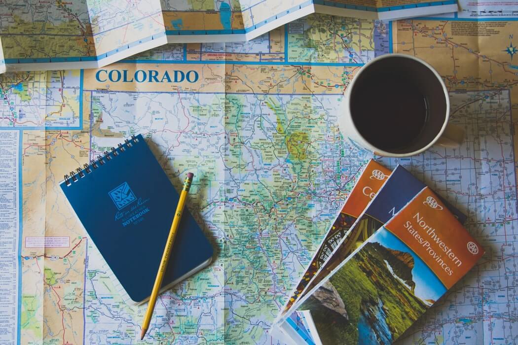 Bloco de notas, lápis e folders turísticos sobre mapa