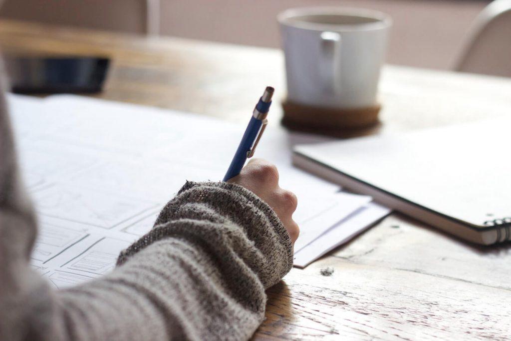 mão escrevendo em papéis