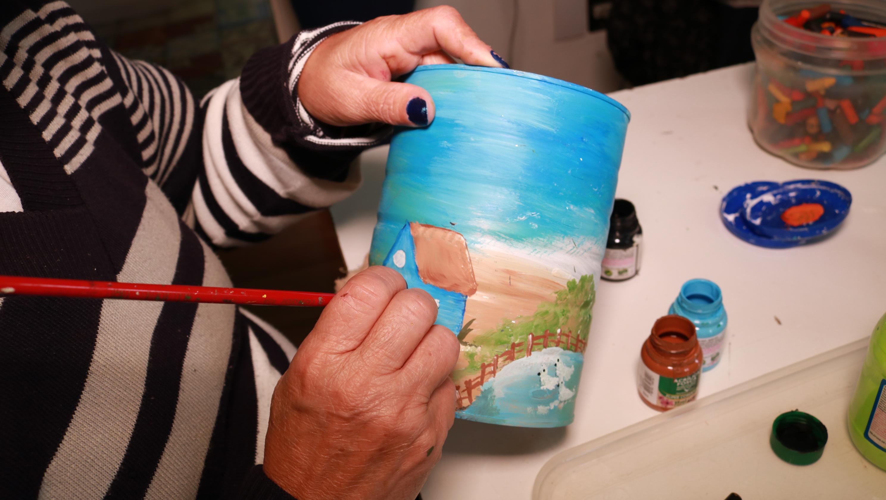 pessoa-pintando-latinha-caps-ucpel