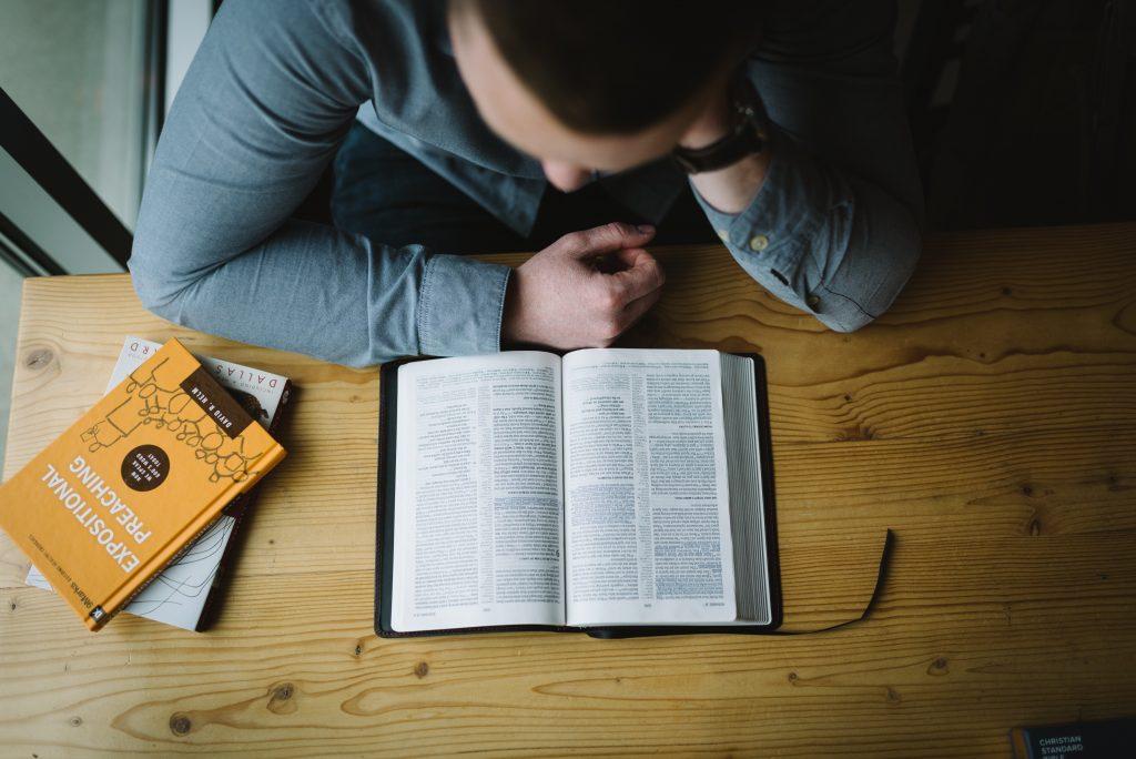 homem lendo, sentado em frente a uma mesa que tem alguns livros em cima dela
