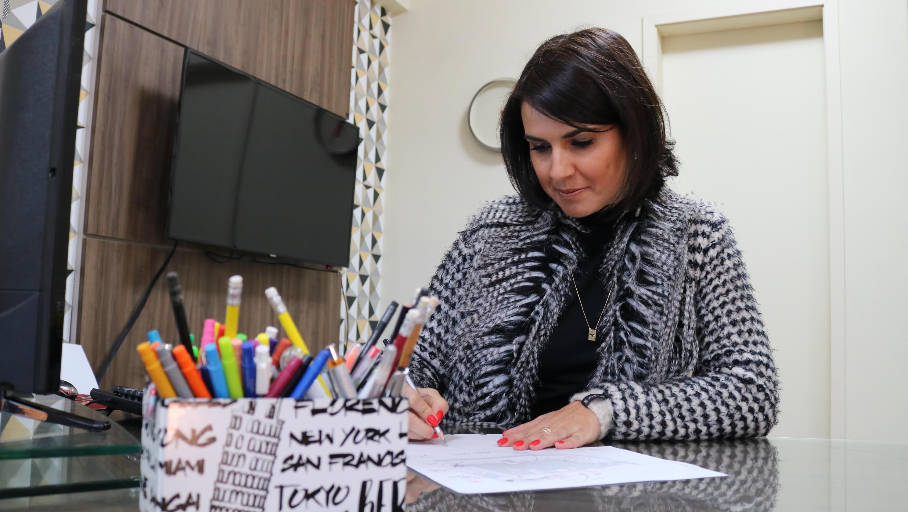 Letícia Arruda - Arquiteta egressa da UCPEL - escrevendo em uma folha