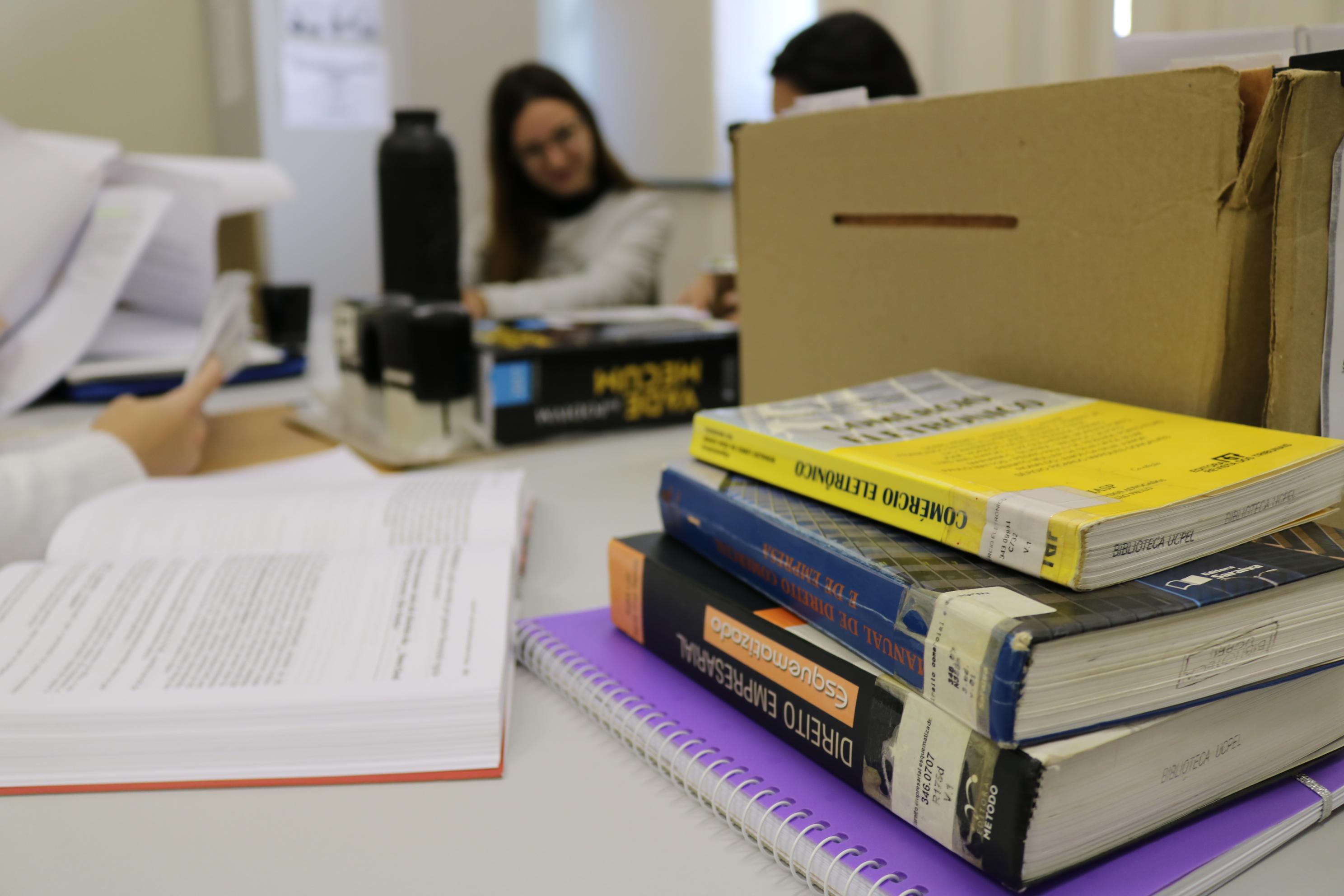 livros sobre direito empilhados em uma mesa com acadêmicas do curso conversando ao fundo