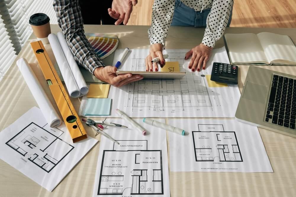 Arquitetos analisando plantas e projetos sobre a mesa.